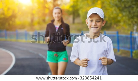 Family, mother and son are running or jogging for sport outdoors