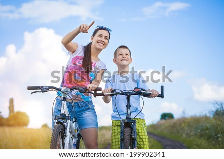 family. mother and son riding  in the park - stock photo