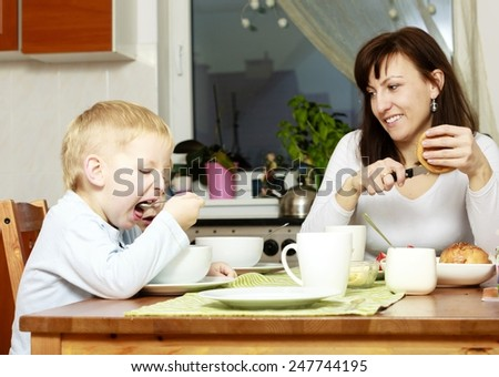 Family mother and two blond brothers boys kids children eating corn flakes and bread breakfast morning meal at the table. Home. - stock photo