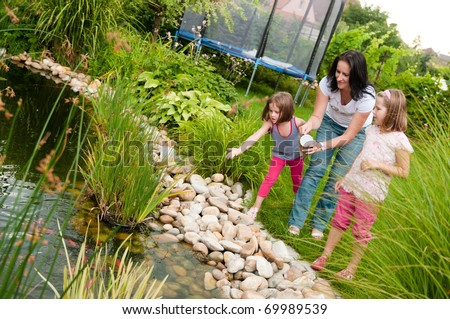 Family (mother and two children) feeding fish in garden pond - stock photo