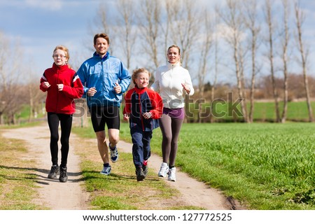 Family, mother, father and children are running or jogging for sport outdoors - stock photo