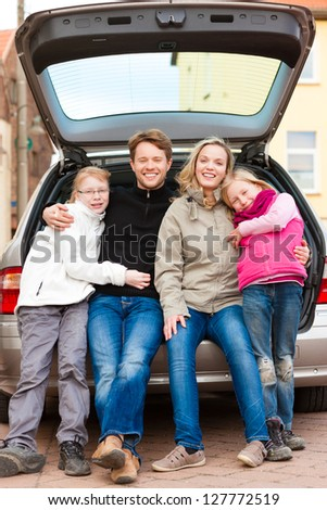 Family, mother, father and children, sitting in the trunk, they make a trip - stock photo