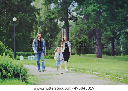 Family - mother, father and daughter walking in the Park full length.