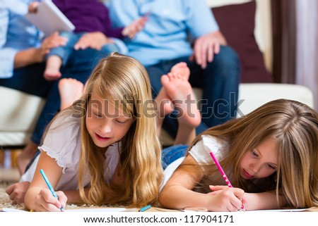 Family, mother, father and daughters are at home, the children coloring on the floor - stock photo