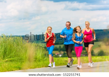Family - mother, father and four children - doing jogging or outdoor sport for fitness on rural street - stock photo