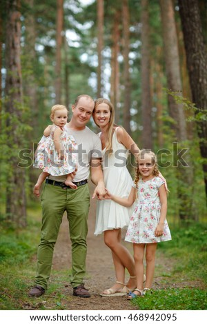 Family - mother, father and two daughters blonde walking through the pine forest in the summer and having fun