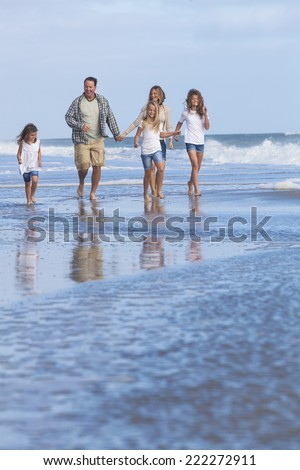 Family mother, father, daughters, parents and female girl children walking in the sea on a beach