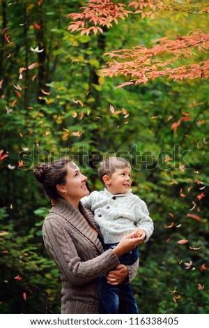 Family. Mother holding a baby in her arms, and they are looking at a beautiful autumn leaves - stock photo