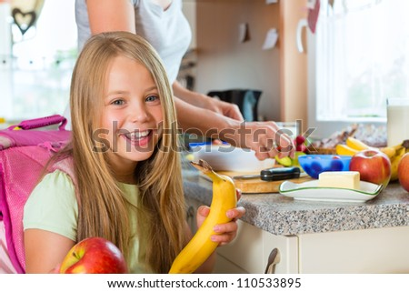 Family - mother making breakfast for her children in the morning and a snack for school - stock photo
