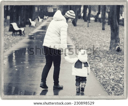 Family Mother with Child in park walking in same clothes black and white - stock photo