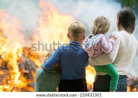 Family mother with children at burning house fire accident background - stock photo