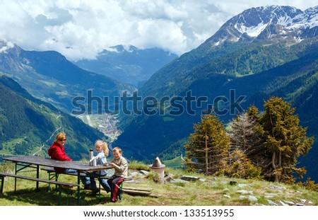 Family (mother with children) rest on summer Alps mountain plateau (Switzerland, Passo del San Gottardo) - stock photo