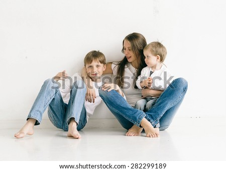 Family mother with children studio portrait full length sitting in jeans on white background - stock photo