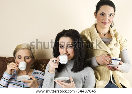 Family mother with daughter drinking hot tea or coffee on couch in living room