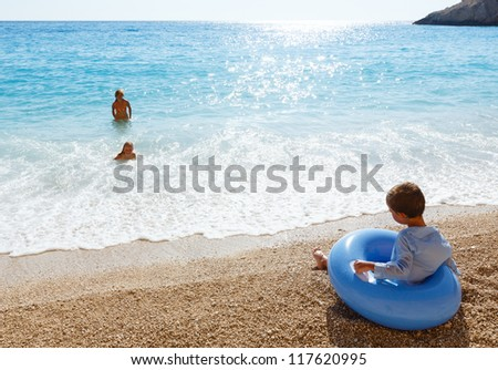 Family (mother with two children) have the water-based recreation on white Egremni beach (Ionian sea, Lefkada, Greece) and sunshine pass in water - stock photo