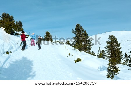 Family  (mother with  two children) plays at snowballs on winter mountain slope