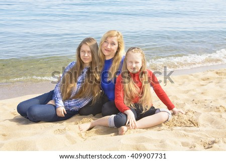 Family mother with two daughters  of sixteen and nine years on beach, European, sit on sea beach.