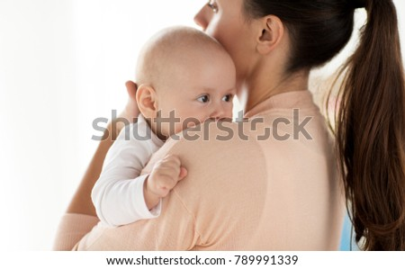 family, motherhood and people concept - close up of little baby boy with mother
