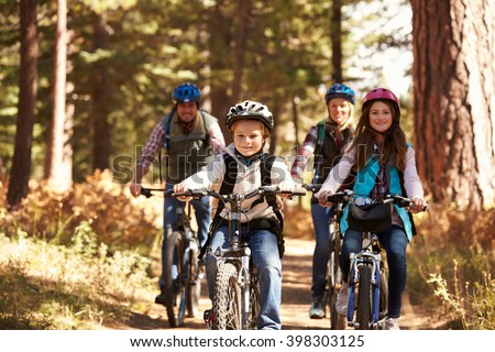Family mountain biking on forest trail, front view - stock photo