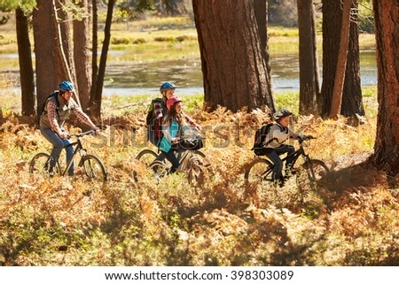 Family mountain biking past lake, California, USA - stock photo