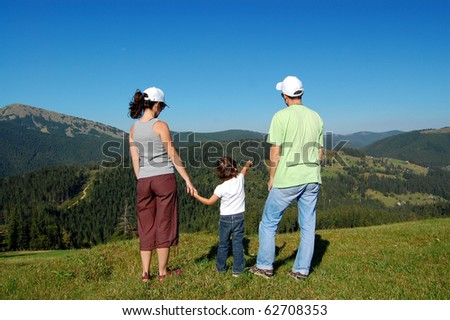 Family mountain vacation. Two parents and a kid walking outdoors - stock photo