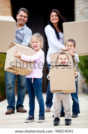 Family moving home and carrying cardboard boxes outdoors - stock photo