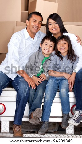 Family moving house with boxes at the back of a truck - stock photo