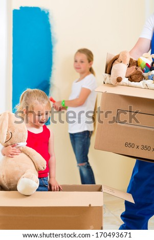 Family moving house with boxes full of stuff, they are painting the walls of their new home - stock photo