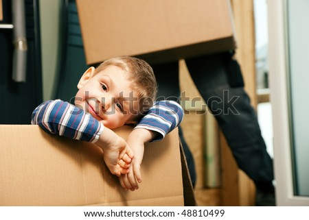 Family moving in their new home. The son is sitting inside a moving box. In the background the father - or a mover (only legs to be seen) is carrying boxes inside the building - stock photo