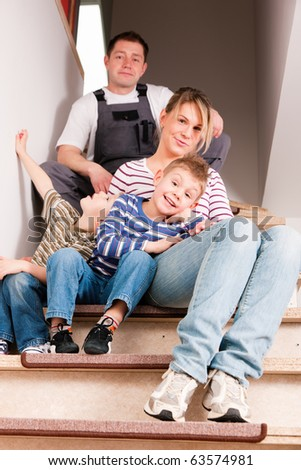 Family moving in their new house. They are sitting on the new stairway which is still not finished - stock photo
