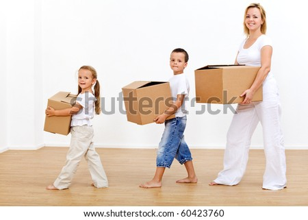 Family moving in to a new home carrying cardboard boxes - stock photo