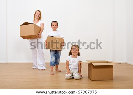 Family moving into a new home carrying cardboard boxes