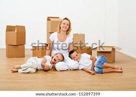 Family moving into a new house - having fun among scattered cardboard boxes - stock photo