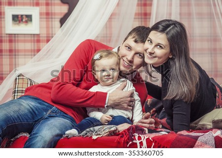 Family mum dad and kid together at home in the cosy atmosphere of the bedrooms in winter interior - stock photo