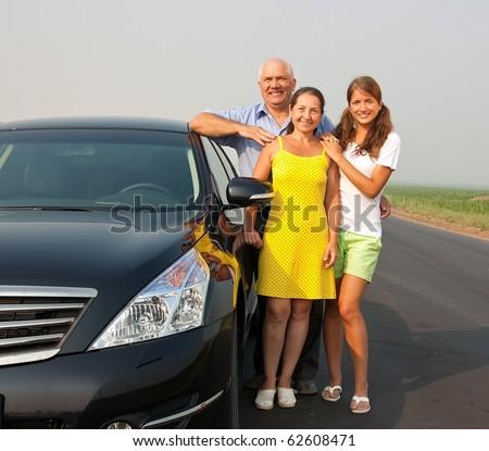 Family near black car at road outdoor - stock photo
