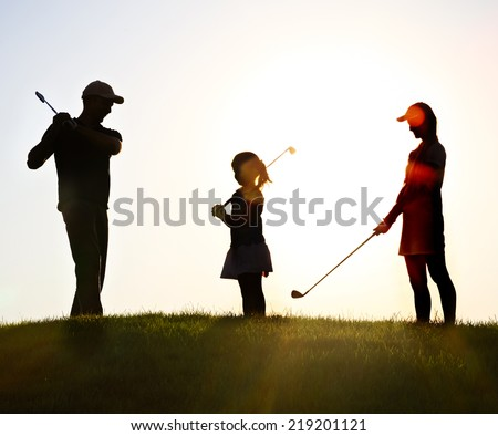 Family of a golfers playing golf at sunset - stock photo
