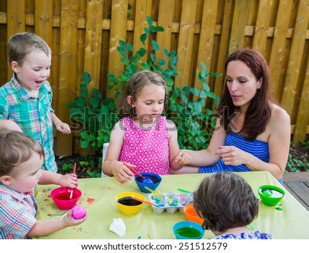 Family of children painting and decorating eggs outside.  Mother and kids have fun as they paint their color dyed Easter eggs during the spring season in a beautiful garden setting.  Part of a series. - stock photo