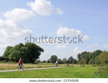 Family of cyclists ride along country lane. - stock photo