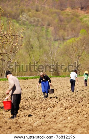 Family of farmers sowing seeds mixed with fertilizer on their land - stock photo