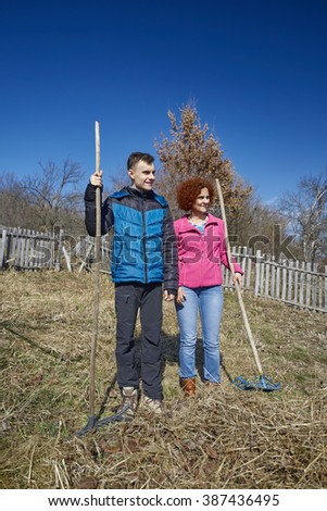 Family of farmers spring cleaning with rakes in an orchard