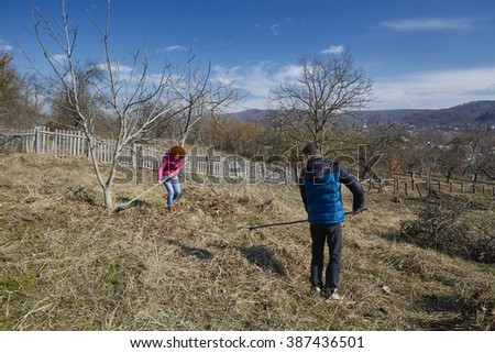 Family of farmers spring cleaning with rakes in an orchard - stock photo