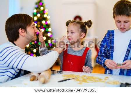Family of father and kids baking cookies at home on Xmas eve. Beautifully decorated room, Christmas tree and lights on background.