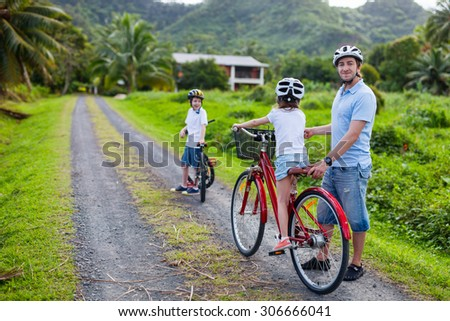 Family of father and kids biking at tropical settings
