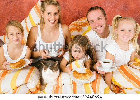 Family of five and their cat having breakfast in their bed in the morning - stock photo