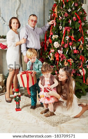 Family of five at room near decorated christmas tree on christmas eve