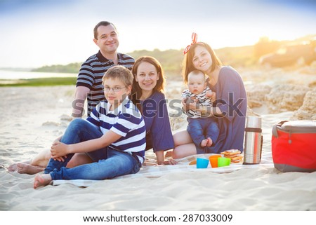 Family of five at the picnic on the beach. Summer vacation concept - stock photo
