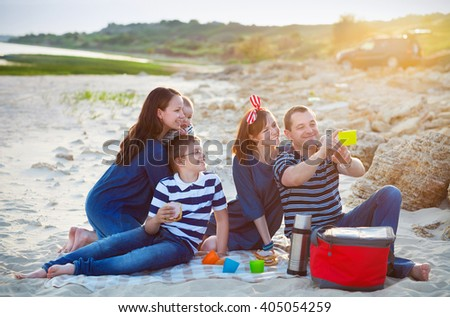 Family of five doing selfy at the picnic on the beach. Summer vacation concept
