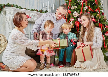 Family of five examines gifts under Christmas tree