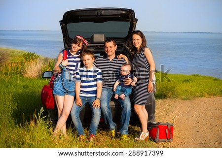 Family of five having fun on the beach going on summer vacation. Car travel and summer vacation concept - stock photo