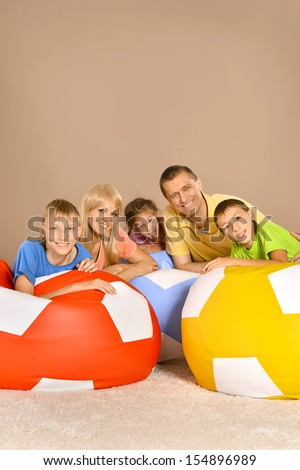 Family of five having fun sitting on colored cushions